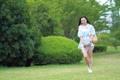 Giovane ragazza attraente cinese dello studente con capelli lunghi che posano in libro di trasporto del parco di verde della citt Fotografia Stock