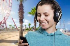 Giovane ragazza attraente con un giocatore su una via della città un chiaro giorno soleggiato che ascolta la musica fotografie stock libere da diritti