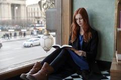 Giovane ragazza attraente della studentessa con il libro nella seduta delle mani immagine stock