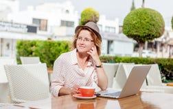 Giovane ragazza attraente in vetri con un computer portatile e una tazza di coff Immagini Stock