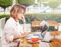 Giovane ragazza attraente in vetri con un computer portatile e una tazza di coff Immagini Stock Libere da Diritti