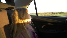 Giovane ragazza bianca che esamina l'automobile dell'azionamento della finestra Sera di autunno di estate di tramonto Tramonto do archivi video