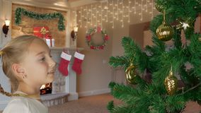 Giovane ragazza bianca emozionante che decora l'albero di Natale e con lo sguardo felice all'albero di abete Preparando per il Bu archivi video