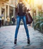 Giovane ragazza bionda alla moda con le gambe lunghe che portano le blue jeans, cappotto marrone di cuoio e tenenti una borsa cam immagini stock