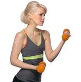 Giovane ragazza bionda atletica che fa gli esercizi con le teste di legno Immagine Stock
