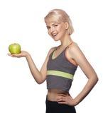 Giovane ragazza bionda attraente che tiene una mela verde in sua mano Immagini Stock