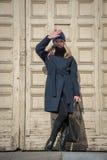Giovane ragazza bionda in cappotto blu con pelliccia in un cappuccio tricottato con la a immagine stock