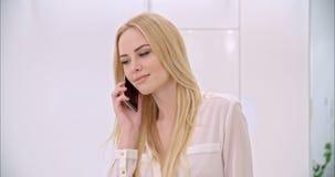 Giovane ragazza bionda che per mezzo del telefono cellulare video d archivio
