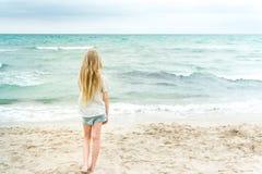 Giovane ragazza bionda che sta sulla spiaggia immagini stock libere da diritti