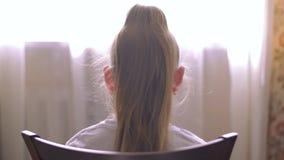Giovane ragazza bionda con la coda dei capelli che si siede sulla finestra anteriore della sedia nell'aula magna Ragazza che si s video d archivio