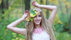 Giovane ragazza bionda con le foglie di autunno ed i capelli lunghi e bei Autunno della ragazza archivi video