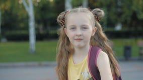Giovane ragazza bionda con uno zaino sulla parte anteriore del parco video d archivio