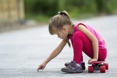Giovane ragazza bionda dai capelli lunghi graziosa del bambino in abbigliamento rosa casuale che si siede sul pattino sulla via p fotografie stock