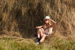 Giovane ragazza bionda del paese in cappello vicino al mucchio di fieno fotografia stock libera da diritti