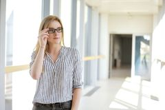 Giovane ragazza bionda dello studente o della donna di affari che esamina macchina fotografica Donna in occhiali da sole in unive Fotografia Stock Libera da Diritti