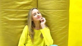 Giovane ragazza bionda fresca e bella su fondo giallo archivi video