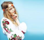 Giovane ragazza bionda graziosa che posa sul fondo blu, fiori di boho di hippy di stile di modo sulla testa fotografia stock