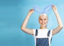 Giovane ragazza bionda graziosa con la posa delle orecchie di coniglio allegra su fondo blu, concetto della gente di stile di vit fotografie stock libere da diritti
