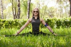 Giovane ragazza bionda nel parco che fa allungamento durante l'allenamento fotografia stock libera da diritti