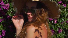 Giovane ragazza bionda in occhiali da sole e cappello di paglia che posano nel giardino di fioritura stock footage