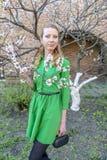 Giovane ragazza bionda sui precedenti di un giardino di fioritura della molla Fotografia Stock