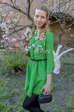Giovane ragazza bionda sui precedenti di un giardino di fioritura della molla Immagine Stock Libera da Diritti