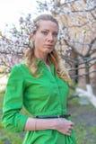 Giovane ragazza bionda sui precedenti di un giardino di fioritura della molla Fotografie Stock