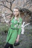 Giovane ragazza bionda sui precedenti di un giardino di fioritura della molla Immagine Stock