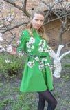 Giovane ragazza bionda sui precedenti di un giardino di fioritura della molla Fotografia Stock Libera da Diritti