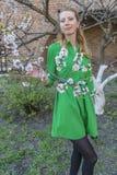 Giovane ragazza bionda sui precedenti di un giardino di fioritura della molla Fotografie Stock Libere da Diritti