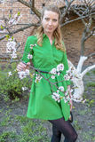 Giovane ragazza bionda sui precedenti di un giardino di fioritura della molla Immagini Stock Libere da Diritti