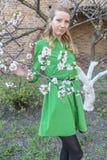 Giovane ragazza bionda sui precedenti di un giardino di fioritura della molla Immagini Stock
