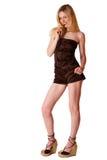 Giovane ragazza bionda sveglia negli shorts marroni su una b bianca Immagini Stock