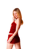Giovane ragazza bionda sveglia in pannello esterno rosso su una parte posteriore di bianco Fotografia Stock