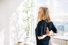 Giovane ragazza bionda vicino alla finestra che fa meditazione Immagini Stock