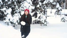 Giovane ragazza carina che sorride, che si diverte a gettare la neve sullo sfondo della foresta invernale e degli alberi coperti  stock footage