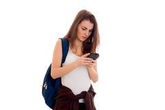 Giovane ragazza castana adorabile dello studente con lo zaino sulle sue spalle che lega con il telefono cellulare isolato su fond Fotografia Stock