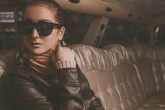 Giovane ragazza castana adulta che distoglie lo sguardo in limousine Fotografia Stock