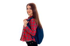 Giovane ragazza castana alla moda dello studente con lo zaino blu che guarda e che posa sulla macchina fotografica isolata su fon Fotografia Stock Libera da Diritti