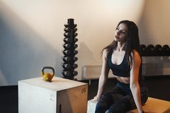 Giovane ragazza castana attraente che si rilassa alla palestra sulla scatola di legno per crossfit dopo l'allenamento Immagine Stock