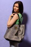 Giovane ragazza castana attraente con la grande borsa della pelle di serpente Fotografie Stock Libere da Diritti
