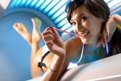 Giovane ragazza castana attraente nel solarium Fotografia Stock