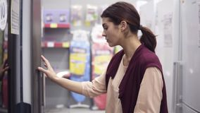 Giovane ragazza castana che cerca il frigorifero perfetto in ferramenta Esamina che ` s dentro il frigorifero bianco osservare stock footage