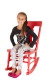 Giovane ragazza castana che si siede nella sedia di oscillazione rosa Fotografia Stock Libera da Diritti