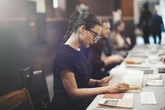 Giovane ragazza castana con i vetri ed il libro di lettura nero del rossetto Fotografia Stock