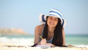 Giovane ragazza castana con la nota e la matita video d archivio