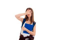 Giovane ragazza castana dello studente con backpackand blu molti libri in sue mani che posano e che esaminano la macchina fotogra Immagine Stock
