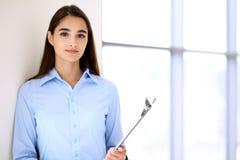 Giovane ragazza castana dello studente o della donna di affari che esamina macchina fotografica Fotografie Stock