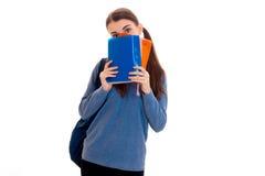 Giovane ragazza castana divertente dello studente con lo zaino sulle sue spalle che nascondono il suo fronte dietro libri isolati Fotografia Stock