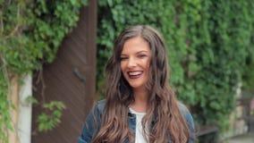 Giovane ragazza castana felice che sorride e che ride esaminando macchina fotografica stock footage